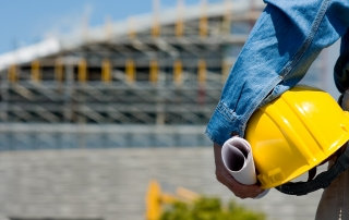 a construction worker on a construction site holding a hard hat a rolled building plans